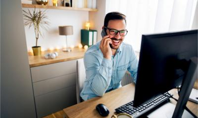 A smiling male employee talks on the phone while working from home