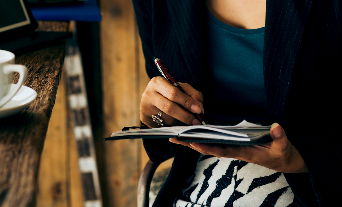 A young business woman checks off her list of strategic objectives to ensure she keeps her business on track