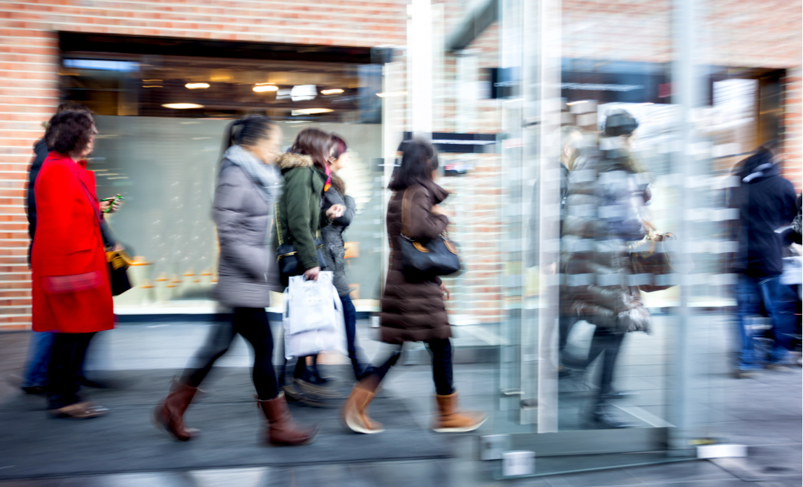Blurred image of shoppers leaving a shopping centre representing customer retention and churn