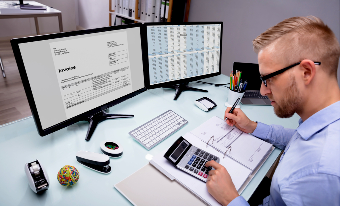 A stressed entrepreneur manually balances his books with a spreadsheet, invoices and calculator.